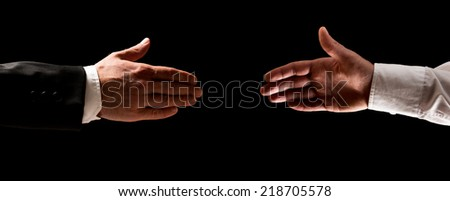 Two men reaching out to shake hands, one in a suit and the other in his shirtsleeves over a dark background. - stock photo