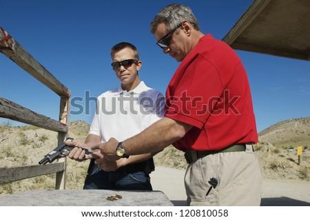 Two men reloading handgun at training - stock photo