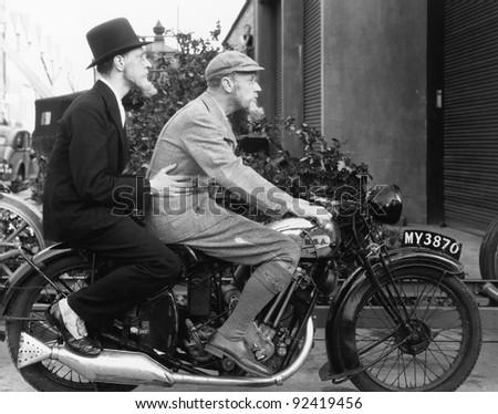 Two men riding a motorbike - stock photo