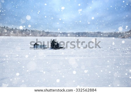 Two men riding on a snowmobile winter river. Winter fishing. Snowmobile trailer. The man in the trailer rests.I can not see people's faces. Snowfall. Copy space. - stock photo