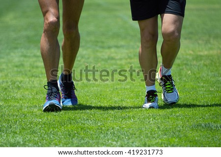 Two men running along the grass in sports shoes