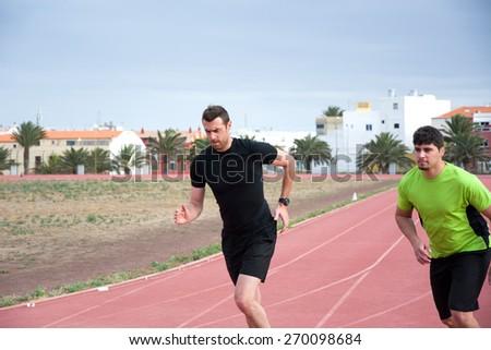 Two men running on running track - stock photo