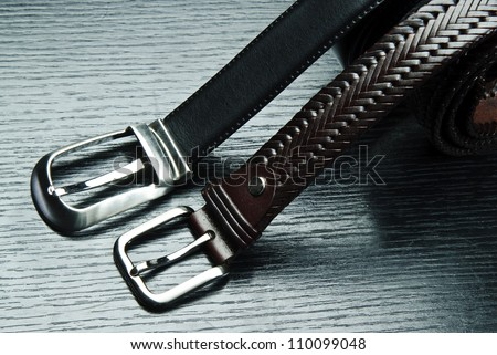 Two men's belts on grey background. - stock photo