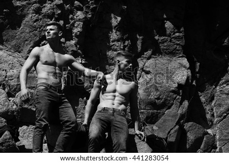 Two men sexy athletic muscular shirtless male twins with bare torso in jeans pose on rocks black and white on mountain background