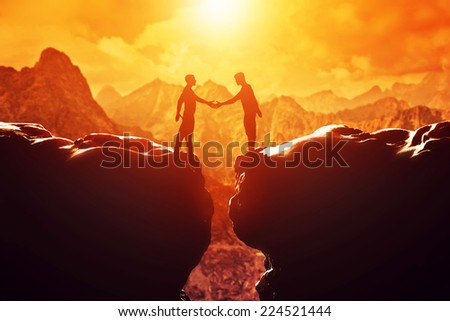 Two men shake hands over precipice between two rocky mountains at sunset. Business, deal, handshake, connection concepts - stock photo
