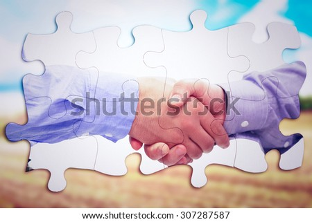 Two men shaking hands against blue sky over fields