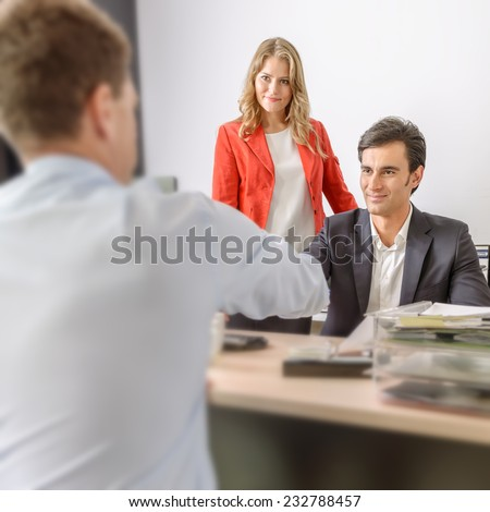 Two men shaking hands in an office and a woman supervising