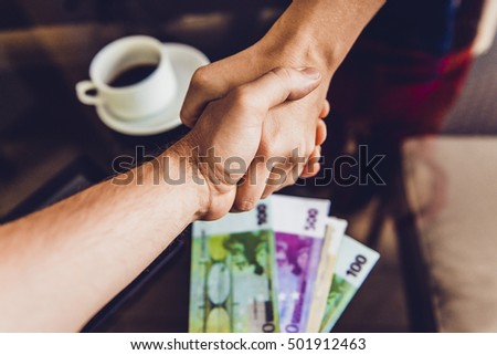 Two men shaking hands in cafe. Conclusion of the agreement, bribe