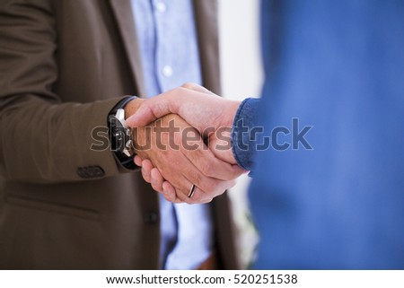 Two men shaking hands in office