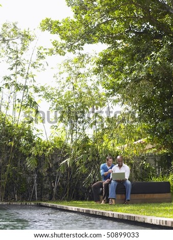 Two men sitting in garden using laptop - stock photo