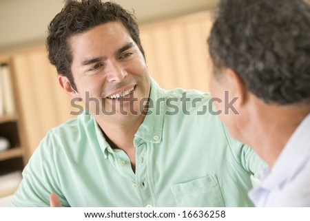 Two men sitting in living room talking and smiling