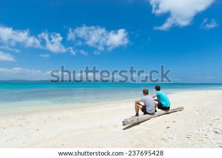 Two men sitting on an idyllic tropical beach in Okinawa, Japan - stock photo