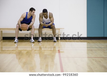 Two men sitting on sidelines of basketball court - stock photo