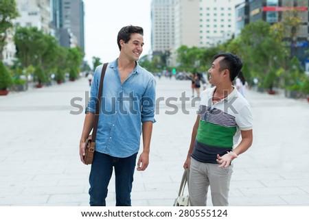 Two men smile talking outdoor, asian mix race friends guys walking city street  - stock photo