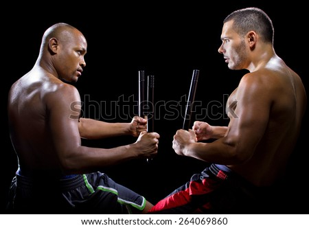 two men sparring with Filipino stick fighting martial arts - stock photo