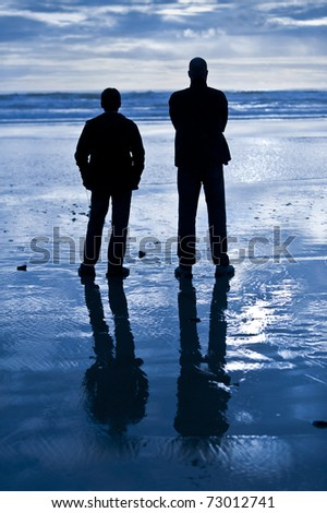 Two men stand on a wet sandy beach and look out towards the ocean. Their silhouettes are reflected on the wet sand. The image is predominantly blue and black. - stock photo