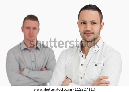 Two men standing while crossing their arms against a white background