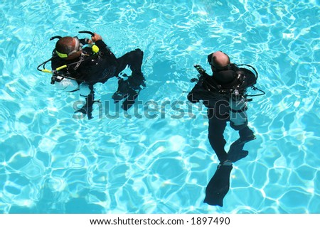 Two men take scuba diving lessons in a pool. - stock photo