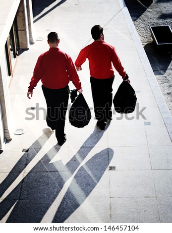 Two men taking out the garbage. - stock photo