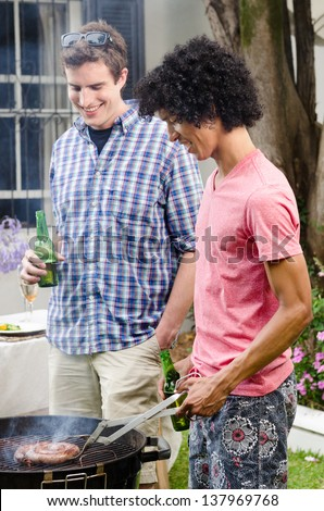 Two men talking and having beers by the bbq at a party, with meat on the smoking grill - stock photo