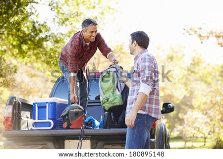 Two Men Unpacking Pick Up Truck On Camping Holiday