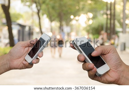 Two men using mobile smart phone with blurred background of people walking on footpath, communication concept, transaction concept. - stock photo