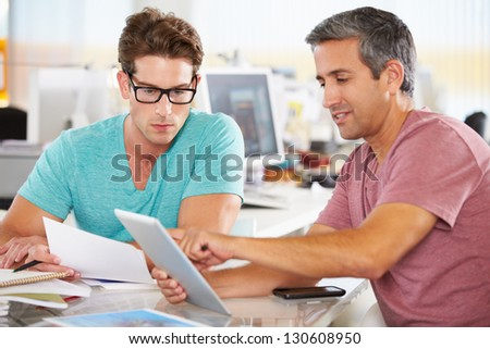 Two Men Using Tablet Computer In Creative Office - stock photo