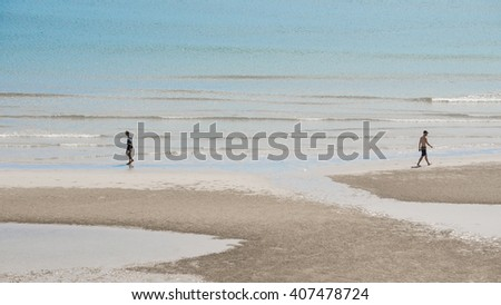 Two men walking along the Hua Hin beach early in the morning , Thailand - stock photo