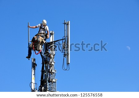 Two Men Working On A Telecommunication Tower