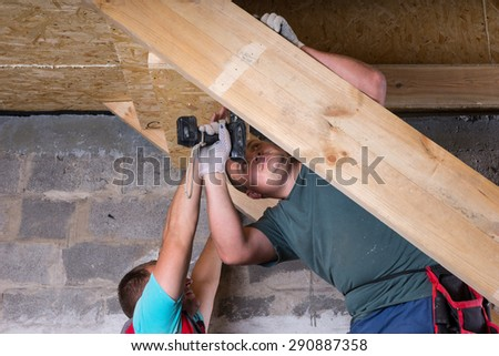 Two Men Working Together to Build Wooden Frame for Stairs with Power Tools, Leading into Basement of Unfinished Home