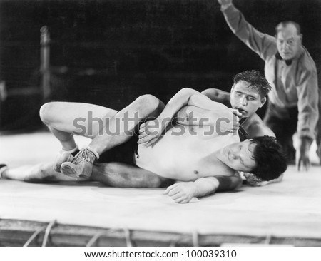 Two men wrestling with a referee in the background - stock photo