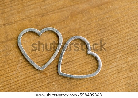 Two metal hearts on a wooden table