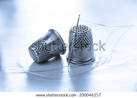 Two metal sewing thimbles and needle with thread