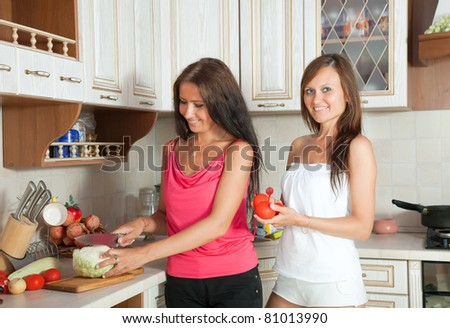 Two mid adult women cooking at them kitchen