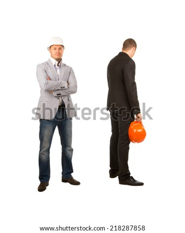 Two Middle Age Engineers with Orange and White Helmets Facing Different Directions. One is Looking at Camera While the Other is Facing at the Back. Isolated on White Background. - stock photo