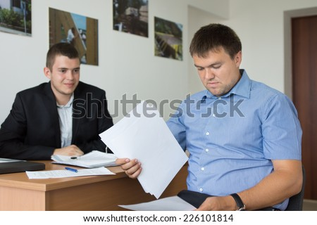 Two Middle Age Male Engineers Reviewing Project Documents at the Office - stock photo