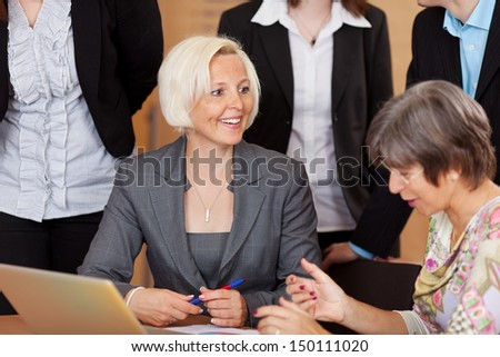 Two middle-aged business women discussing a project surrounded by other employees - stock photo