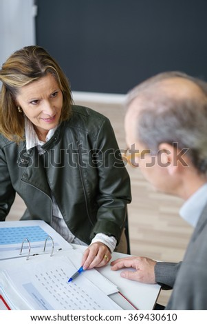 two middle-aged co-workers sitting at desk talking about documents
