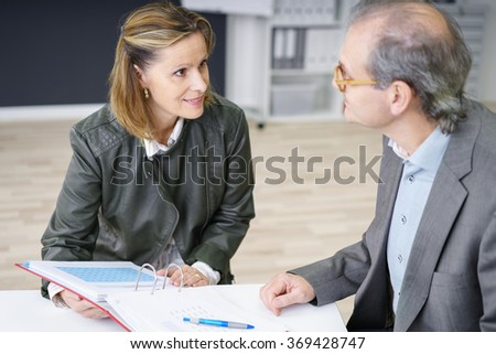 two middle-aged colleagues working on documents in the office