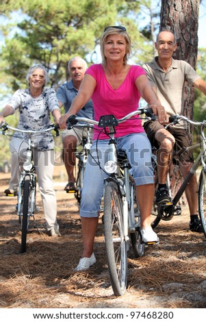 Two middle-aged couples riding bicycles - stock photo