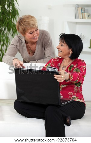 Two middle aged friends shopping online.