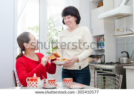 Two middle-aged  girlfriends drinking tea in   kitchen.