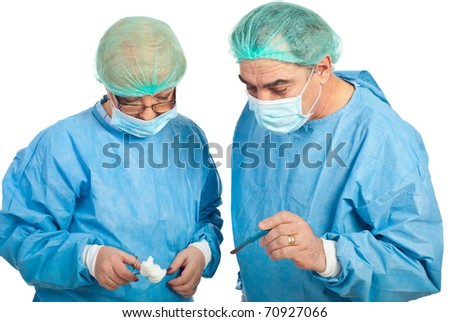 Two middle aged surgeons in surgery holding scalpel and forceps isolated on white background
