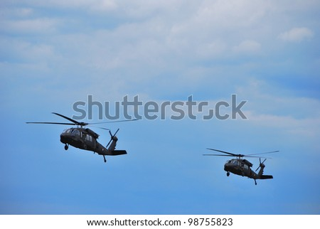 two military helicopters fly together at air show