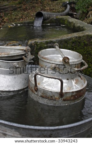 two milk-churns in the tub - stock photo