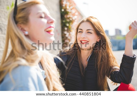 Two millennials young women blonde and brunette friends outdoor in city backlight chatting and laughing - focus on brunette - friendship, happiness, conversation concept - stock photo