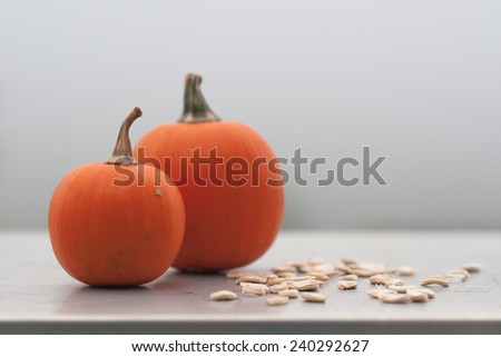 Two mini pumpkins and pumpkin seeds, selective focus.