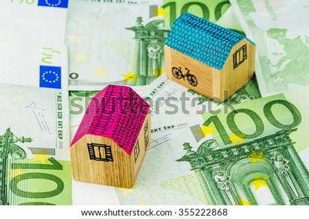 two miniature houses laying on one hundred euro banknotes - stock photo