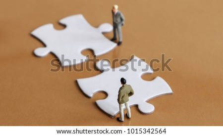 Two miniature people and two puzzle pieces.