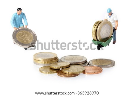 Two Miniature workers drives euro coins in wheelbarrow - stock photo